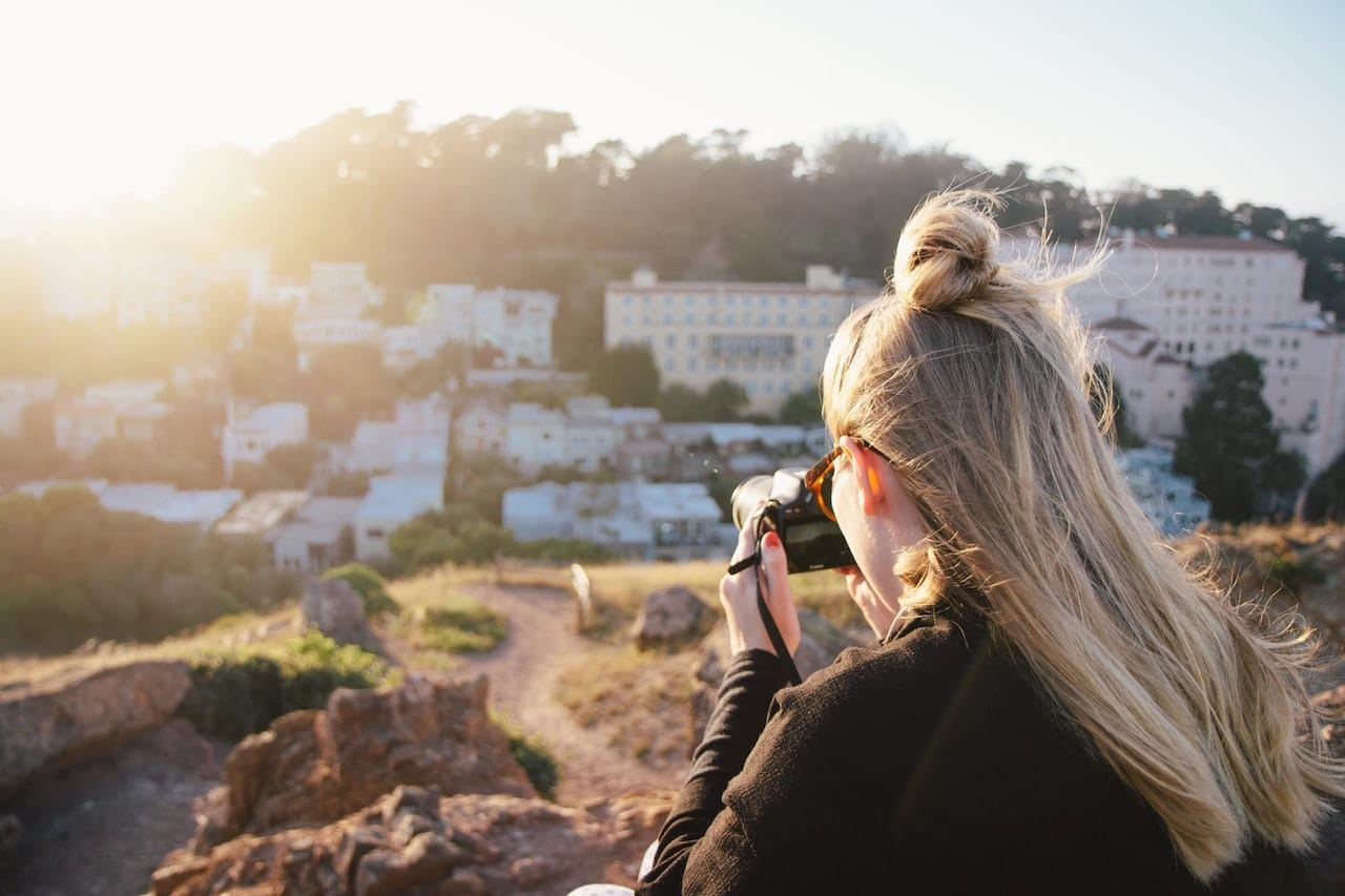 Woman in black jacket taking photo of city during daytime