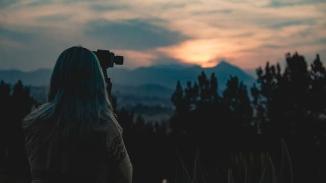 Landscape photo of a camera woman at sunset
